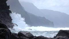 SLOW MOTION: Strong wave splashing into coarse ocean cliff upcoming from the sea - stock footage