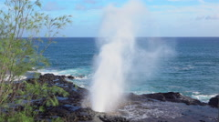 SLOW MOTION CLOSE UP: Turquoise ocean splashing through volcanic rocky blowhole Stock Footage