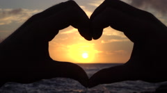 SLOW MOTION: Young man capturing beautiful golden sun with heart shaped hands - stock footage