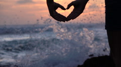 SLOW MOTION: Young girl shapes heart with hands over beautiful evening sky Stock Footage