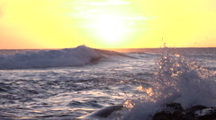 SLOW MOTION CLOSE UP: Ocean waves hitting into rocky shore at golden sunset Stock Footage