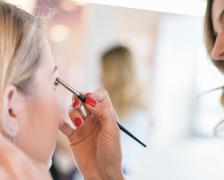 Applying eyeshadow in a beauty salon. Stock Photos