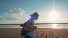 Young attractive woman walking on the beach during sunset, slow motion Stock Footage
