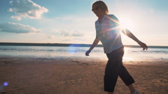 Young attractive woman running and having a lot of fun on the beach during sunse Stock Footage