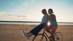 Young woman and man riding a bicycle at the shore and having some fun, slow moti - stock footage
