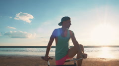 Young man with vintage bike at the beach near the sea or lake during sunset - stock footage
