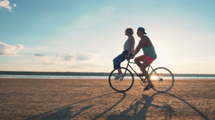 Young woman and man riding a bicycle at the shore and having some fun, slow moti Stock Footage