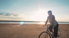 Young attractive woman riding vintage bike on the beach near the sea during sunr - stock footage