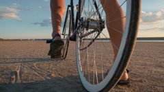 Close up shot of man riding vintage bike at the beach during sunset or sunset Stock Footage