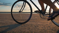 Close up shot of man riding vintage bike at the beach during sunset or sunrise - stock footage