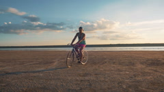 Young man riding vintage bike at the beach near the sea or lake during sunset - stock footage