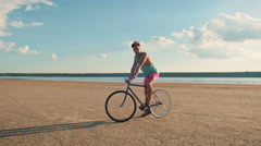Young man riding vintage bike at the beach near the sea or lake during sunrise - stock footage