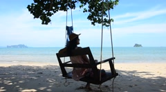 Thai woman sit and relax on wooden bench swings at the beach Stock Footage