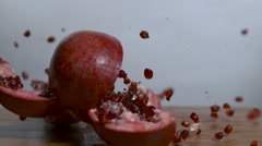 Pomegranate falls onto cutting board intact but cut and bursts, spewing seeds - stock footage