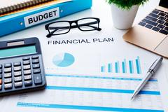 Financial and budget planning concept with calculator laptop and finacial rep - stock photo