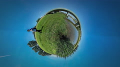 360Vr Video Tourist is Talking on Phone Walking by Field Bridge Through River Stock Footage