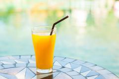 Orange juice on color stone table Stock Photos