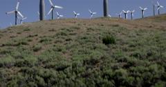 Tilt up to smaller wind turbines on hillside setting in Mojave Desert 4K Stock Footage