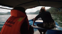 Tourist in a safety jacket in a boat with a guide going to Trunyan cemetery Stock Footage