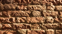 Wall of red brick ,in the beam of light. Wall of the shooting. - stock footage