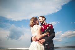 Just married wedding couple walking on the beach at sunset Stock Photos