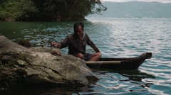 Traditional fishing on Lake Batur, one fiserman in a small boat, editorial Stock Footage