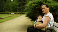 Mother breastfeeds baby, sitting on a bench at the park Stock Footage