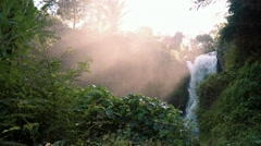 Water spray and mist rising from Tegenungan Waterfall, Ubud, Bali - morning Stock Footage