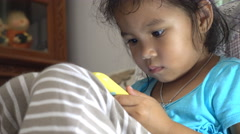 Little girl attentively watching cartoons on a mobile phone Stock Footage