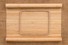 Frame made of rope lying on a bamboo mat in the form of manuscript - stock photo
