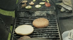 Hamburger patty on the grilling pan with open flames Stock Footage