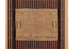 Frame made of burlap lying on a bamboo mat in the form of manuscript Stock Photos