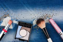 Still life from cosmetics on ragged jeans with rhinestones Stock Photos