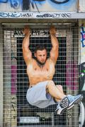 Strong sportsman doing abs exercise outdoor Stock Photos