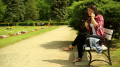 Young woman doing a scene on the phone on a bench in the park Stock Footage