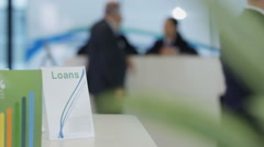 4K Bank with customers & staff, printed material in foreground Stock Footage