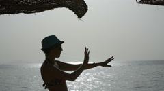 Dancing silhouette beautiful girl at sunrise near the sea Stock Footage