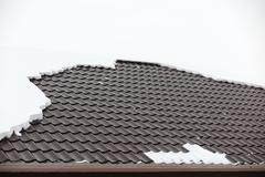 Modern roof covered with tile effect PVC coated metal roof sheets with snow Stock Photos