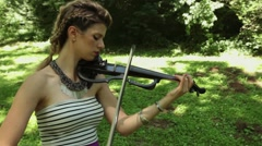 Attractive female classical musician plays electric violin outdoors Stock Footage