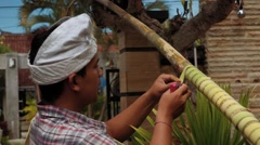 Balinese man making penjor on Galungan Day - covering pole with palm ribbon Stock Footage