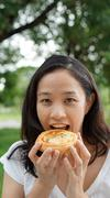 Asian woman mature adult eating bread carbohydrates Stock Photos