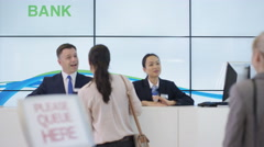 4K Bank customers queuing to talk to friendly staff at service desk Stock Footage