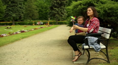 Mother Sitting At The Bench With Her Baby On Knees And Play With Him Stock Footage