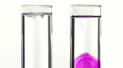 Potassium permanganate and  methylene blue fall in water of two test tube Stock Footage