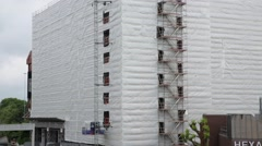 Scaffolding around a wrapped building  and an industrial lift Stock Footage