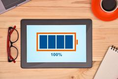tablet and battery with level indicator - stock photo