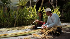 Balinese man and woman cutting branches to decorate penjor on Galungan Day - stock footage