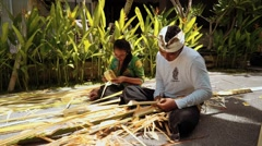 Balinese man and woman making palm leaf decorations for a penjor on Galungan Day - stock footage