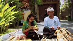 Balinese man and woman making palm leaf decorations for a penjor on Galungan Stock Footage
