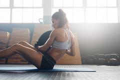 Fitness woman working out on core muscles Stock Photos
